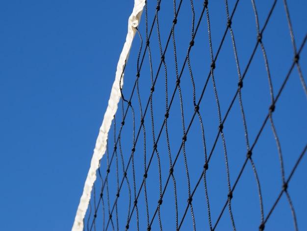 Rete da pallavolo su una spiaggia tropicale contro il cielo blu.