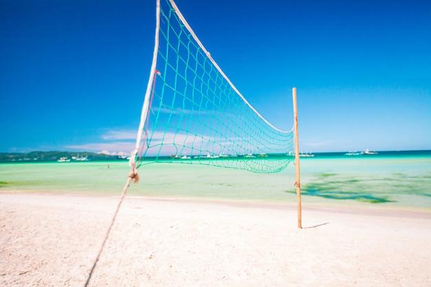 Rete di pallavolo del primo piano alla spiaggia esotica tropicale vuota