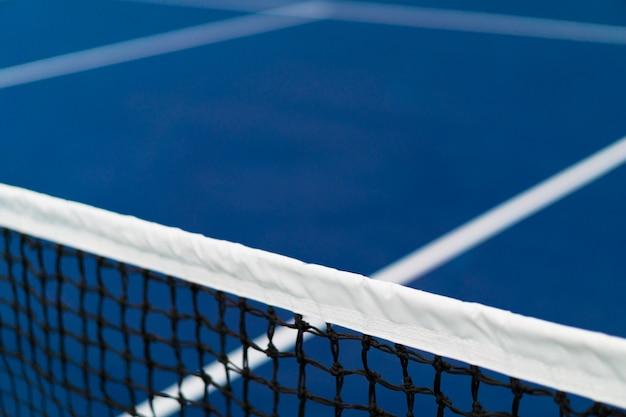 Rete diagonale di tennis con la banda bianca nel campo da tennis in terra battuta blu, concetto della concorrenza di tennis