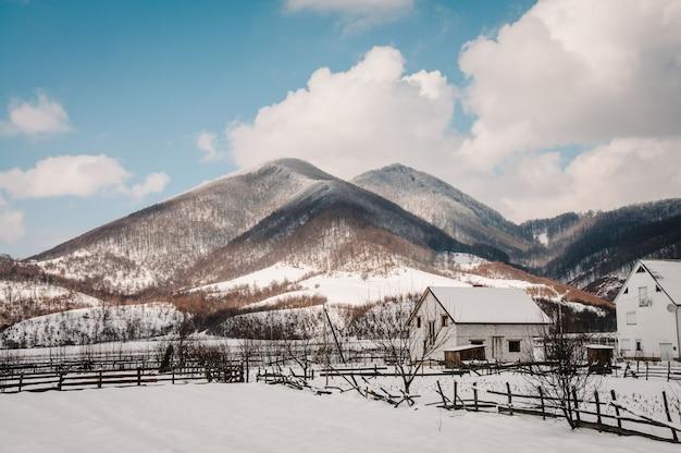 Rete fissa di legno innevata, case nelle montagne dei carpazi ucraina