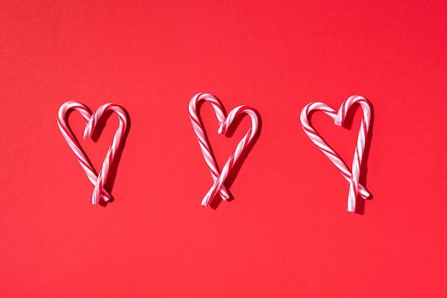 Reticolo di natale del bastoncino di zucchero con forma del cuore su fondo rosso