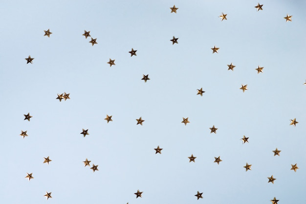 Reticolo di natale fatto delle stelle dorate sull'azzurro