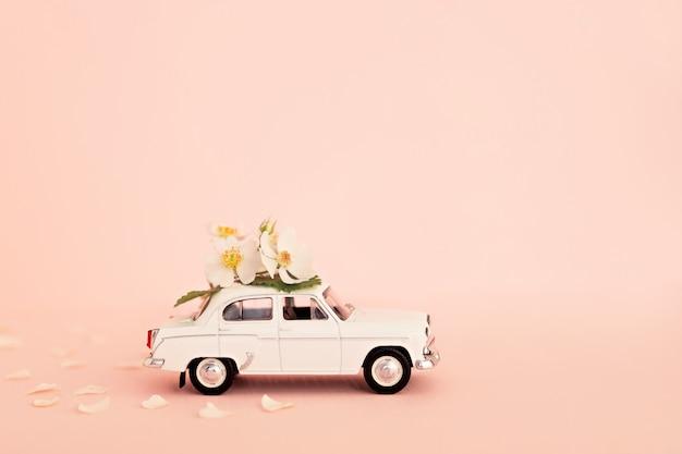 Retro automobile bianca del giocattolo che trasporta i fiori e regali su una priorità bassa dentellare