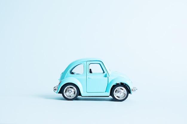 Retro automobile blu del giocattolo sul blu