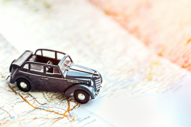 Retro automobile di cabrio del giocattolo sulla mappa, concetto di turismo