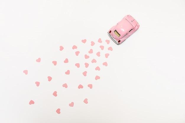 Retro automobile rosa del giocattolo che consegna i cuori su fondo rosa. carta di san valentino
