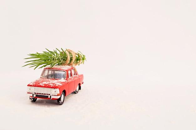 Retro automobile rossa del giocattolo di consegna dell'albero di natale su una priorità bassa bianca in inverno con neve