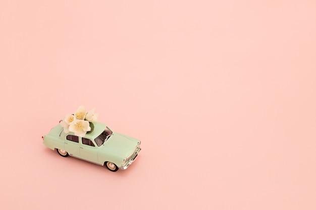Retro automobile verde del giocattolo che trasporta i fiori e regali su una priorità bassa dentellare