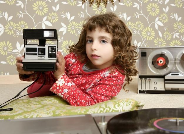 Retro bambina della foto della macchina fotografica nella stanza d'annata