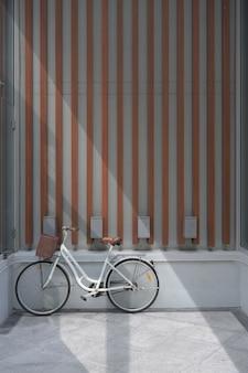 Retro bicicletta anteriore in cemento e parete in legno.