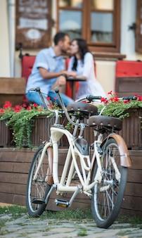 Retro bicicletta in tandem vicino a fiori rossi. coppia che si bacia