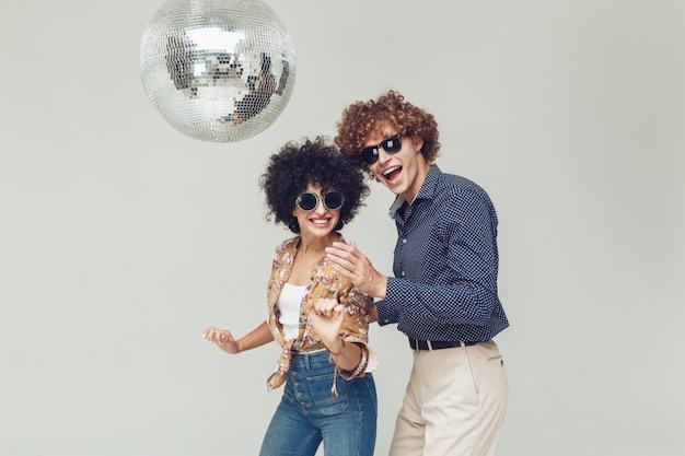 Retro coppie amorose sorridenti emotive che ballano vicino alla palla della discoteca.
