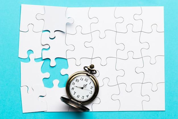 Retro cronometro sul puzzle bianco incompleto sopra fondo blu
