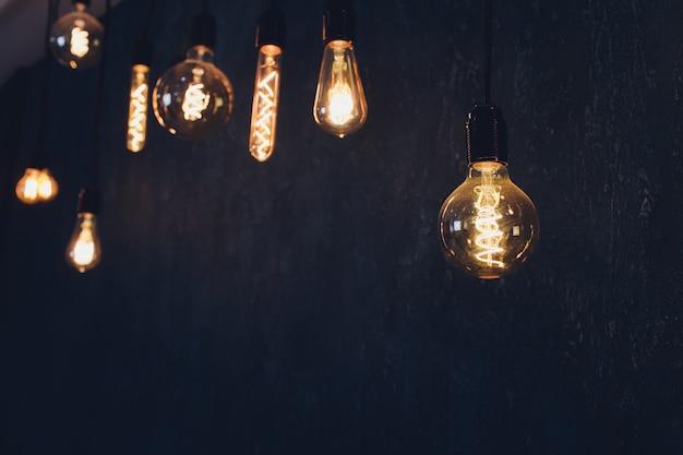 Retro decorazione d'annata del filamento di edison della lampadina sul fondo del muro di mattoni. decorazione di illuminazione.