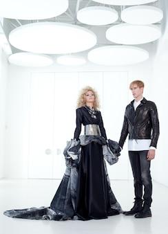 Retro futurista haute couture nera coppia in sala bianca moderna con ispirazione vampiro