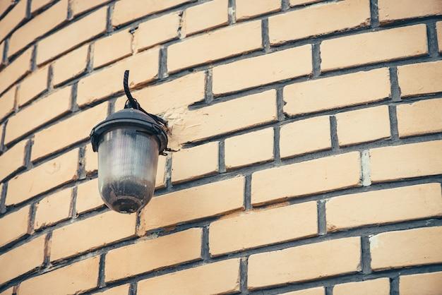 Retro lampada di via sul muro di mattoni beige della fine della costruzione su con lo spazio della copia. mattoni arrotondati imperfetti con lampione vintage.