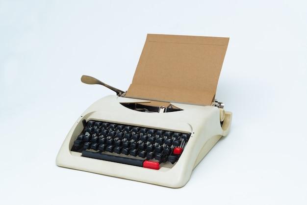 Retro macchina da scrivere con foglio di carta bianca su bianco.