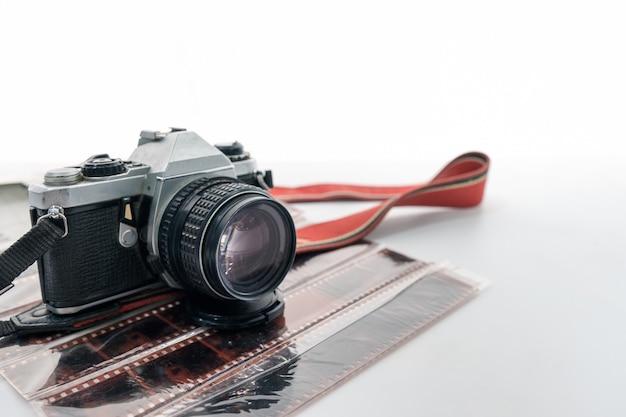 Retro macchina fotografica con cinturino rosso sul negativo del film