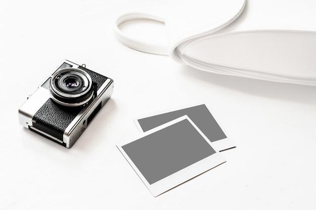 Retro macchina fotografica d'annata di flatlay su fondo bianco di legno con la foto di carta istantanea vuota