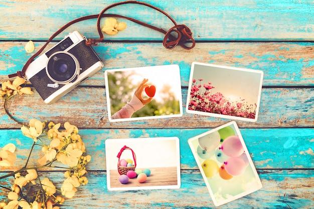 Retro macchina fotografica e album di foto di carta sulla tavola di legno con i fiori