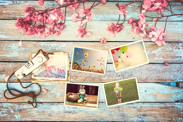 Retro macchina fotografica e album di foto di carta sulla tavola di legno con il disegno del confine dei fiori