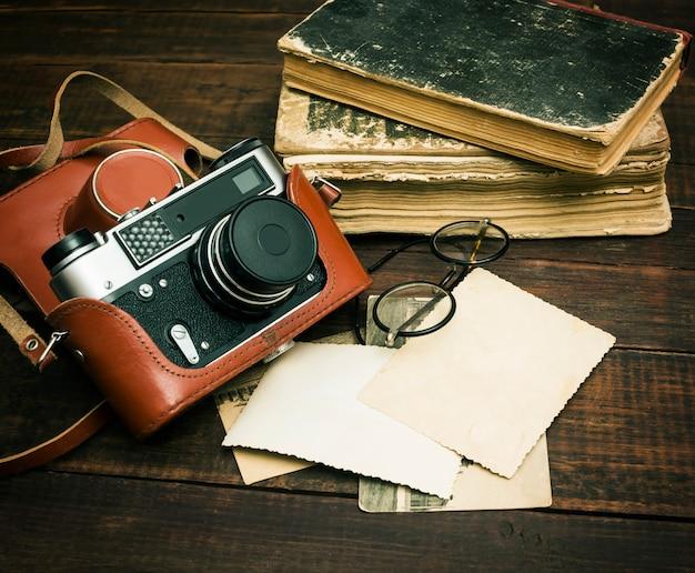 Retro macchina fotografica tranquilla e alcune vecchie foto sulla tavola di legno