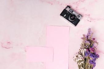 Retro macchina fotografica vicino a carte e mazzo di fiori