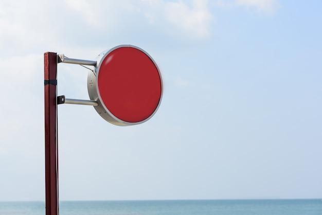 Retro segnale stradale rosso sopra il fondo blu del cielo del mare