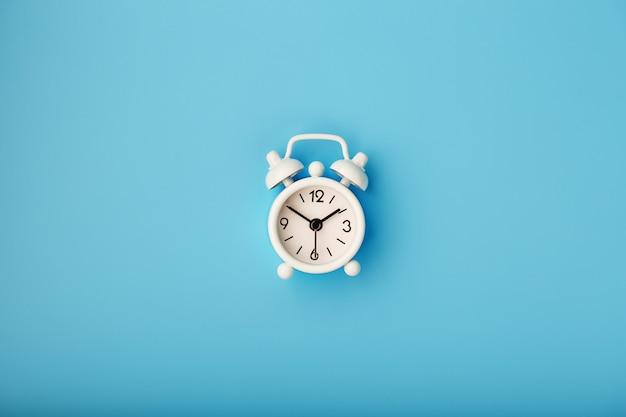 Retro sveglia bianca su fondo blu. concetto di tempo con spazio libero per il testo.