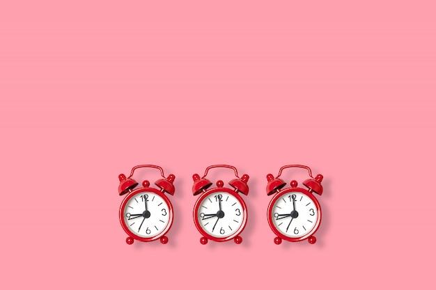 Retro sveglia distesa piana bella nuova su uno spazio rosa della copia