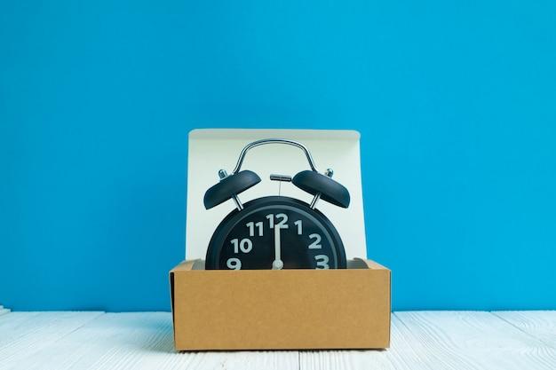 Retro sveglia in scatola di cartone o vassoio marrone di consegna su legno bianco e sul fondo blu della parete, sul tempo e sul concetto di scadenza.