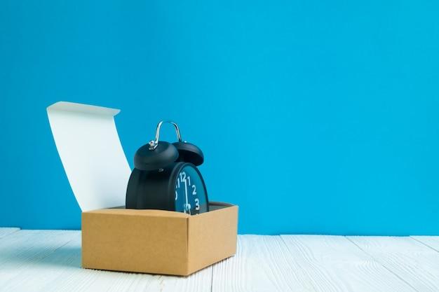 Retro sveglia nella scatola di cartone marrone di consegna o vassoio su legno bianco e sul fondo blu della parete