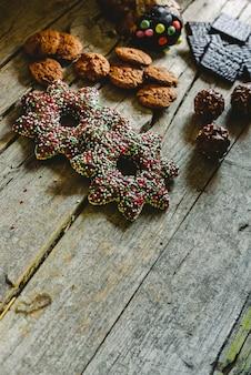 Retro tavola di legno invecchiato con biscotti al cioccolato e caramelle in un angolo con spazio per il testo