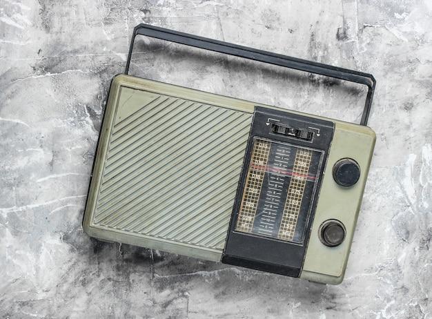 Retro vecchio radioricevitore su una superficie di calcestruzzo grigia. vista dall'alto. tecnologia obsoleta