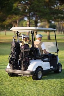 Retrovisione degli amici maschii del giocatore di golf che si siedono in carrozzino di golf