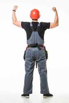 Retrovisione del giovane operaio premuroso che cerca sul fondo bianco
