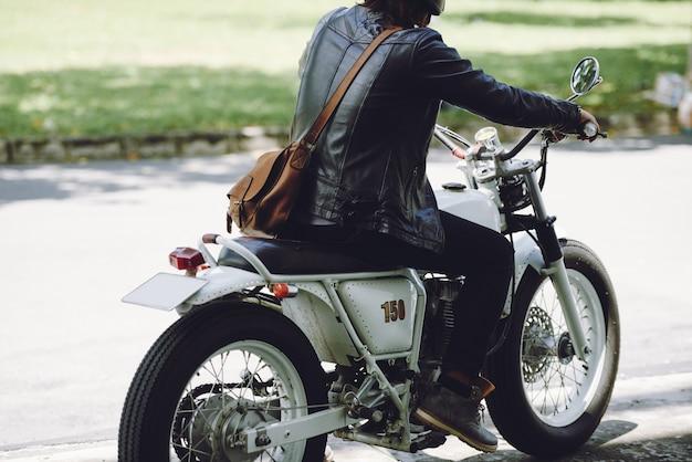 Retrovisione del motociclista maschio che guida sulla motocicletta lungo la strada