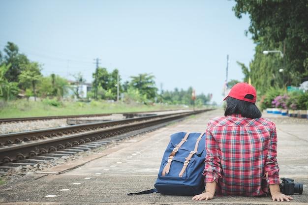 Retrovisione del turismo della giovane donna (passeggero) che si siede sulla piattaforma alla stazione ferroviaria
