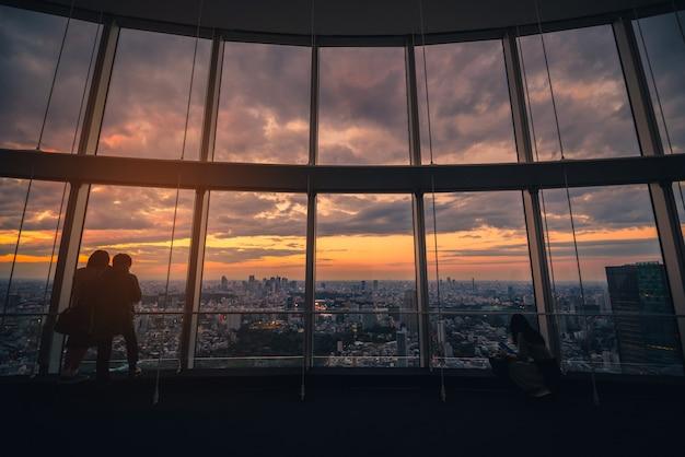 Retrovisione del viaggiatore che guarda l'orizzonte di tokyo e la vista dei grattacieli sulla piattaforma di osservazione al tramonto nel giappone.