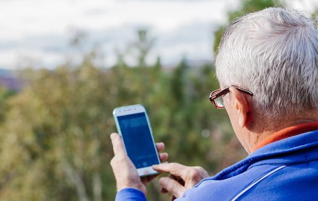 Retrovisione dell'uomo anziano che prende una foto con il suo telefono cellulare