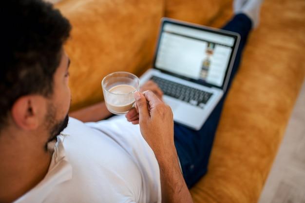 Retrovisione dell'uomo che si siede sul sofà a casa che beve caffè e che per mezzo del computer portatile.