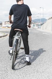 Retrovisione dell'uomo che si siede sulla bicicletta sopra la strada diritta