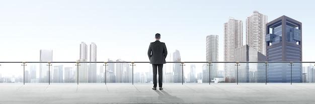 Retrovisione dell'uomo d'affari asiatico che sta sul terrazzo moderno e che esamina vista