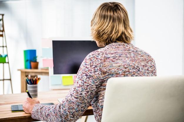 Retrovisione dell'uomo d'affari dei pantaloni a vita bassa facendo uso della grafica della compressa nel suo ufficio