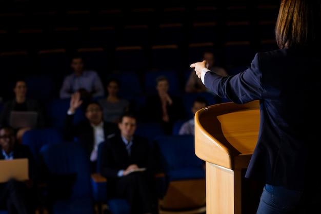 Retrovisione dell'uomo d'affari femminile che dà un discorso