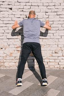 Retrovisione dell'uomo dell'atleta che si appoggia il muro di mattoni mentre facendo esercizio