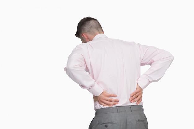 Retrovisione dell'uomo di affari con dolore alla schiena sopra fondo bianco