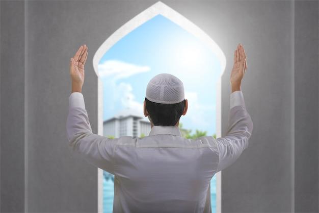 Retrovisione dell'uomo musulmano asiatico che sta mentre mani e pregare sollevate
