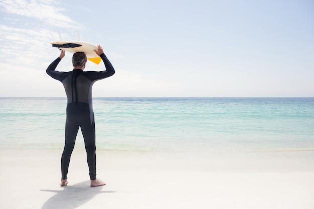 Retrovisione dell'uomo senior che tiene una tavola da surf sopra la sua testa