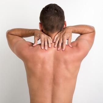 Retrovisione dell'uomo senza camicia che ha dolore alla schiena che sta contro la parete bianca